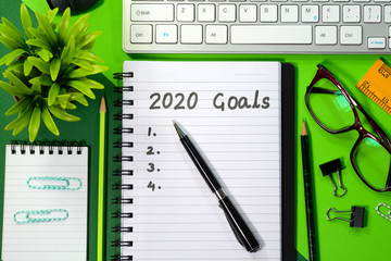 2020 Goals written on a diary in a desk