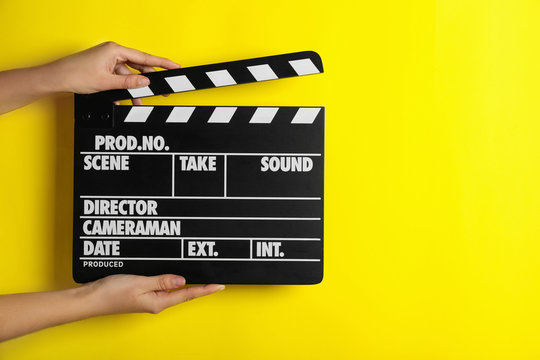Woman holding clapperboard on yellow background, closeup with space for text. Cinema production