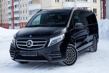 Front view of new a expensive Mercedes Benz V-class minivan bumper and hood of a car, a long black limousine, model outdoors, prepared for sale on a sunny winter day