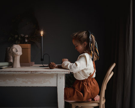 Little girl in old fashioned clothes siting at table by candlelight