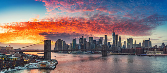 Panoramic view on Brooklyn bridge and Manhattan at vibrant sunset, New York City