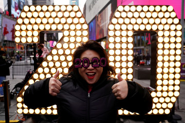 A woman poses for photos with the numerals 2 and 0 for News Year's Eve in Times Square in the Manhattan borough of New York City