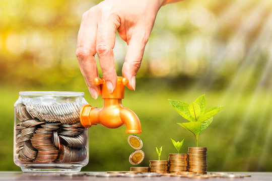 Woman's hand open a faucet of jar and gold coin drop for invest with growing money and seed put on the wood in the public park, for currency and financial business investment and fund concept.