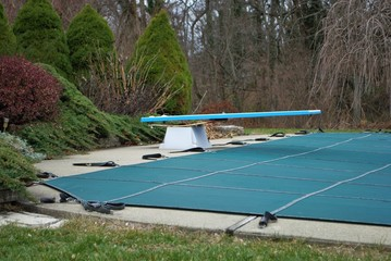 backyard swimming pool with diving board and pool slide tarped up and closed down for winter Wall mural