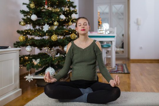 Practicing yoga during pregnancy. Christmas holiday and exercising concepts.