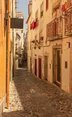 Aluminium Prints Narrow alley Narrow residential alley in the Alfama district in summertime, Lisbon City Centre.