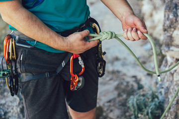 Close-up of climber with climbing equipment, tying knot on climbing harness, preparing for climbing.