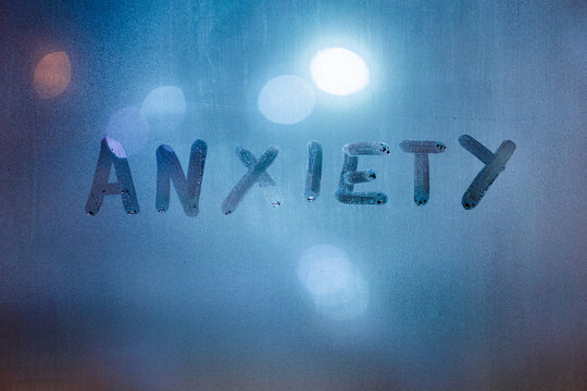 the word anxiety written by finger on night wet glass with blurred classic blue lights in background