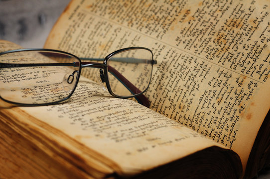 Open book with optical glasses. Old medieval Bible in Armenian language. selective focus, shallow depth of field, not protected by copyright