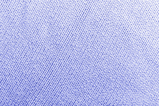 Classic blue knitted fabric wool texture for background. Close up of blue knitted material pattern for design. Blue warm sweater textile background. Texture of painted textile cloth waves. blue toning