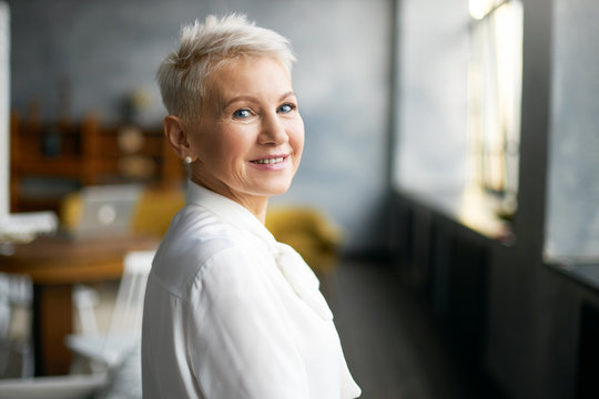 Indoor shot of fashionable successful mature blonde woman in formal white blouse turning head to camera with welcoming friendly smile, giving tour around her office. People, age, career and employment