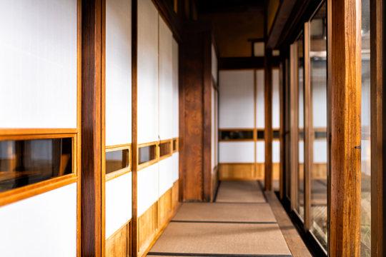 Traditional japanese home or ryokan with shoji sliding paper doors tatami mat floor in corridor hallway leading to room by glass windows