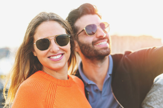Beautiful couple of young people wearing sunglasses enjoying life in the summer. She's looking at the camera.