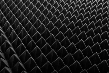 Abstract background in the form of pyramids and dragon scales. Acoustic black foam rubber.