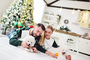 a young couple in love in Christmas sweaters with reindeer playing with cute Samoyed puppies lying on the warm floor against the background of a Christmas tree and a modern kitchen.