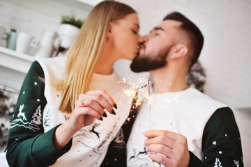 a pair of young lovers in Christmas sweaters with a picture of deer kissing on the background of sparklers.