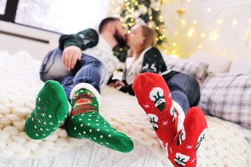a young couple kissing lying on a bed against the background of a Christmas tree in colored Christmas socks with a picture of deer and snowmen close up