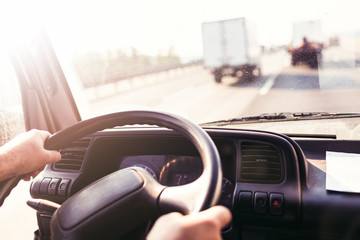 Male driving a truck and holding steering wheel of truck or lorry during the movement in the road. Image with selective focus on the wheel, dashboard with speedometer and tachometer, blurred