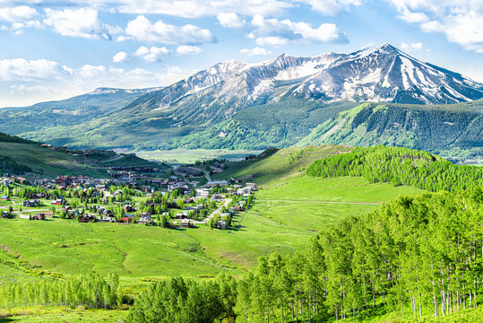 Crested Butte, Colorado town cityscape high angle view from Snodgrass hiking trail in summer with alpine meadows and aspent trees forest grove