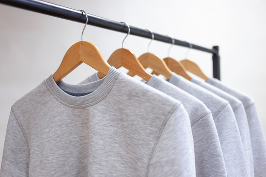 Blank sweatshirts hanging on a hanger in the wardrobe or showroom