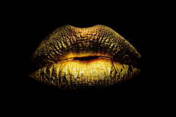 Gold Paint from the lips. Golden lips on beautiful model girls mouth. Make-up. Beauty makeup close up. Golden make up in lips. Gold concept. Wall mural