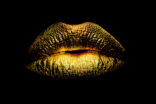 Gold Paint from the lips. Golden lips on beautiful model girls mouth. Make-up. Beauty makeup close up. Golden make up in lips. Gold concept.
