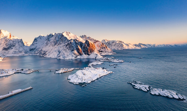 Amazing aerial view of Lofoten Islands nature from drone, winter sunrise snowy scenery of village Reine, Sakrisoy and Hamnoy during beautiful mountain ridge with alpenglow, scene over polar circle.