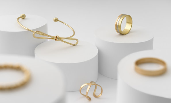 Modern Golden bow shape bracelet and rings collection on white cylinders platform