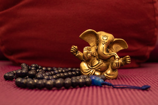 Golden Ganesha statue with blue mala beads on yoga mat in front of a yoga pillow. Close up of Meditation accessories.