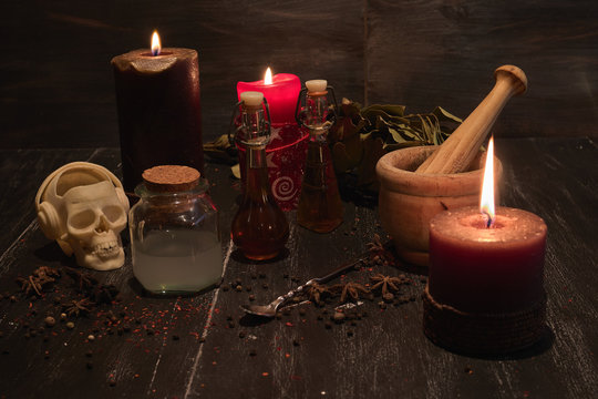 potion of natural herbs for black magic with candles, mortar, metal glass skull and olive oil