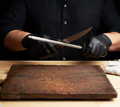chef in a black shirt and black latex gloves sharpen a kitchen knife on an iron sharpener