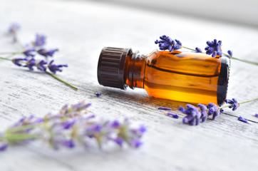 Keuken foto achterwand Lavendel Organic lavender essential oil in dark glass transparent bottle and fresh lavender flowers on wooden background. Aromatherapy treatment.