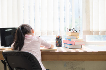Girl sitting on her desk in the room.