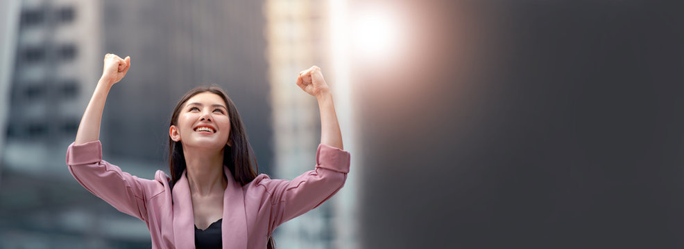 Power of woman, young Asian businesswoman raised arms motivates herself with  confident.