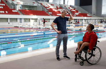 Apple's CEO Tim Cook speaks with Singapore Paralympian Theresa Goh at the OCBC Aquatic Centre, Singapore Sports Hub