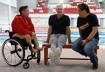 Apple's CEO Tim Cook, Singapore Paralympian Theresa Goh and blogger Kin Mun Lee, also known as Mr Brown, chat at the OCBC Aquatic Centre, Singapore Sports Hub