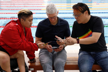 Apple's CEO Tim Cook, Singapore Paralympian Theresa Goh and blogger Kin Mun Lee, also known as Mr Brown, share a selfie photo via Airdrop at the OCBC Aquatic Centre, Singapore Sports Hub