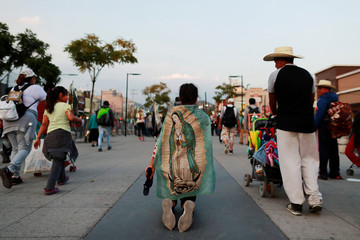 A woman walks on her knees with the Virgin of Guadalupe on her back towards the Basilica of Guadalupe during the annual pilgrimage in honor of the Virgin of Guadalupe, patron saint of Mexican Catholics