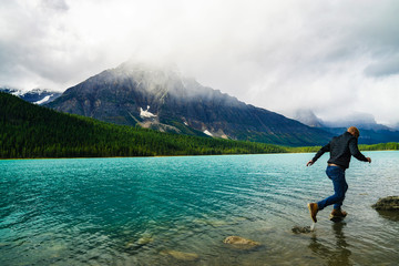 Man Running On Rocks In Beautiful Lake With Epic Peaks In The Wild Fun Outdoor Concept