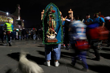 A man stands with an image of the Virgin of Guadalupe at the Basilica of Guadalupe during the annual pilgrimage in honor of the Virgin of Guadalupe, patron saint of Mexican Catholics, in Mexico City