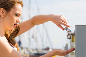 Woman drinking water from tap in marina.
