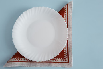 A white empty plate on a linen napkin