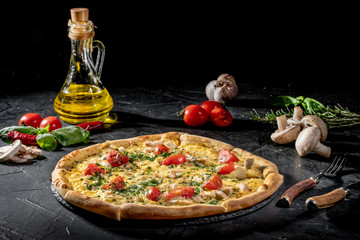Tasty traditional italian pizza with salami, cheese, tomatoes greens on a dark background