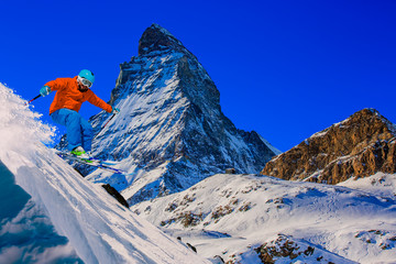 Spoed Fotobehang Donkerblauw Man skiing on fresh powder snow with Matterhorn in background, Zermatt in Swiss Alps.