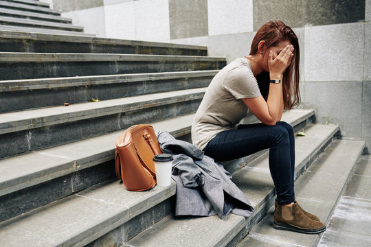 Pretty young woman sitting on steps outdoor and covering face when crying after difficult break up