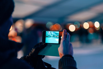 male hands holding a mobile phone on photo camera mode - man taking picture of a ice skating rink by night