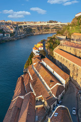 old houses with red tiled roofs on the steep banks of the Douro River in the historical part of the Portuguese city of Porto