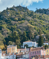 beautiful houses near a hill overgrown with forest with an old fortress on top in the Portuguese town of Sintra