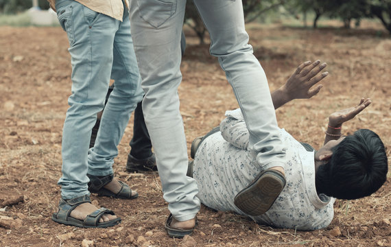 Concept of mob lynching - Group of people bullying, kicking a man - Close up of young adult males hitting a person on ground