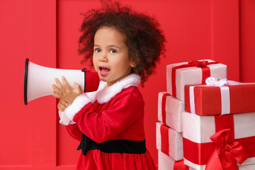 Little African-American girl in Santa costume, with gifts and megaphone on color background